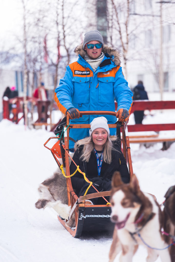 Torkil Hansen riding the dog sled with a happy tourist.
